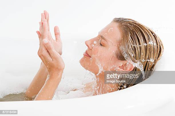 A woman splashing water on her face