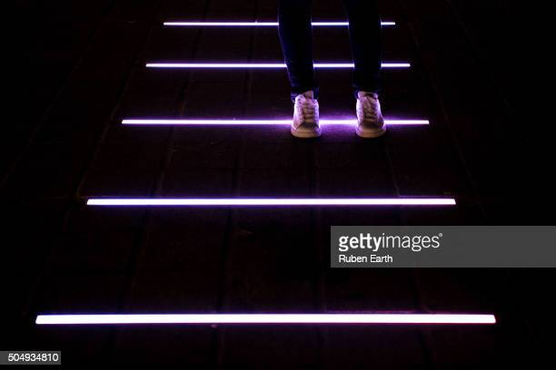 a woman sport shoes magenta ground led light reflection - futurism stock photos and pictures