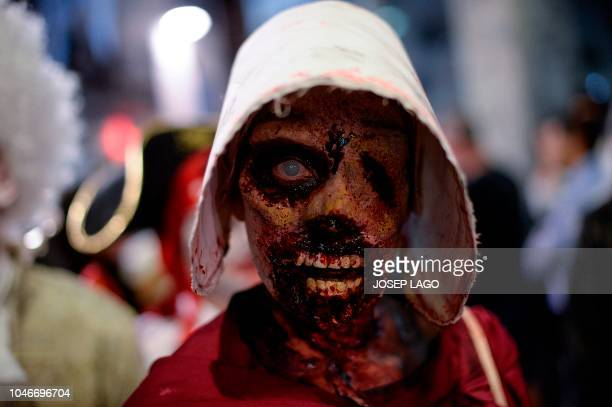 TOPSHOT A woman sporting zombie makeup and dressed up as characters of the US TV series The Handmaid's Tale take part in the Zombie Walk event on...
