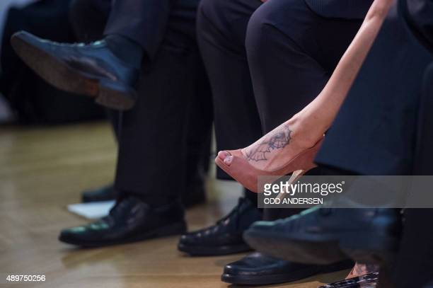 A woman sports a tattoo as she and other entrepreneurs and business men listens to US automotive and energy storage company Tesla's CEO Elon Musk the...