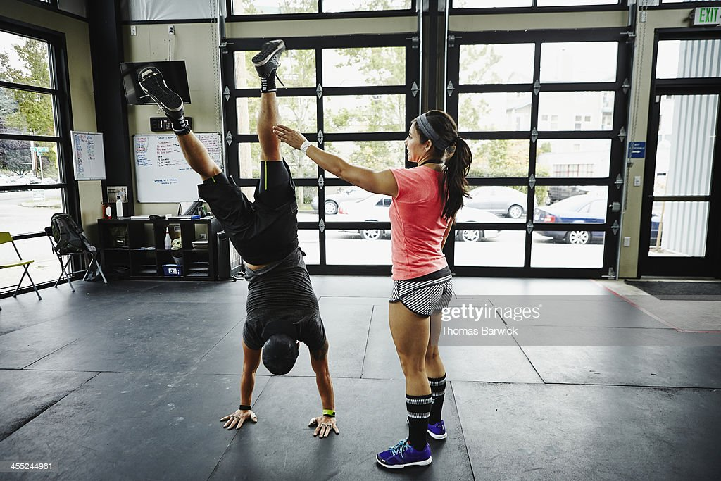 Woman spotting man doing handstand in gym gym