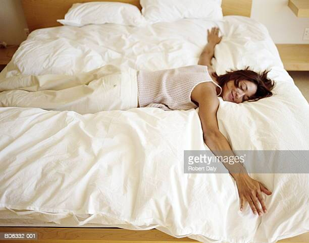Woman sprawled on bed, smiling