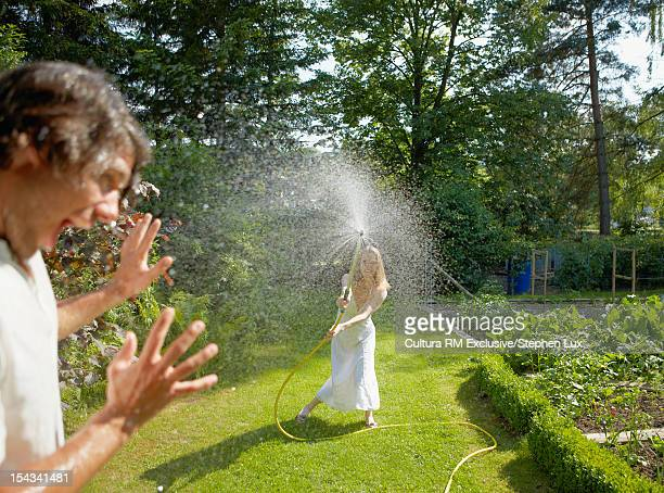 Woman spraying boyfriend with hose