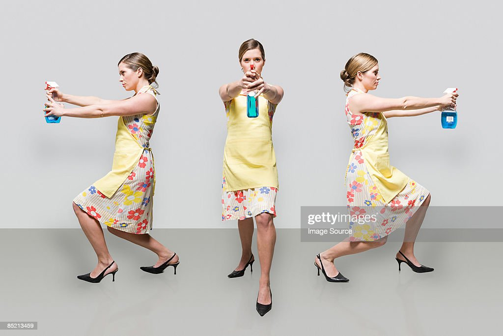 Woman spraying cleaning product : Stock Photo