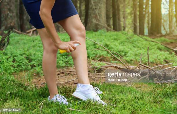 woman spraying insect repellent on ankle and foot outdoors. - insect bites images stock pictures, royalty-free photos & images