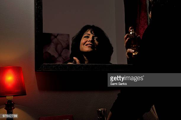 Woman spraying perfume in front of mirror
