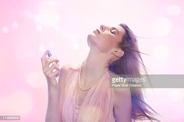 woman spraying perfume on her neck - pink dress stock photos and pictures