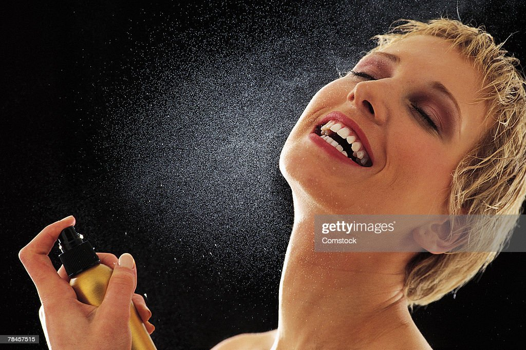 Woman spraying perfume on her neck : Stock Photo