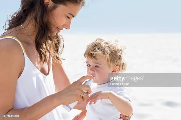 Woman spraying sunscreen on her baby hand