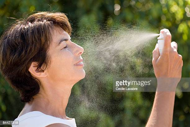 Woman spraying water on face