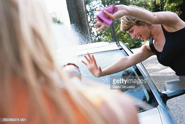 Woman spraying water onto woman
