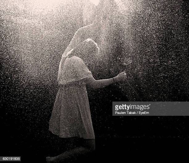 woman spraying water through gardening hose - paulien tabak foto e immagini stock