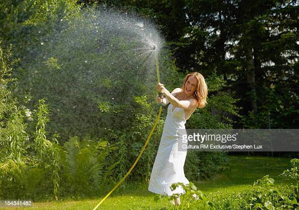 Woman spraying with hose in garden