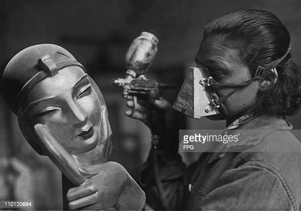 Woman spray-painting an art deco bust to be used in a shop display, 1929.