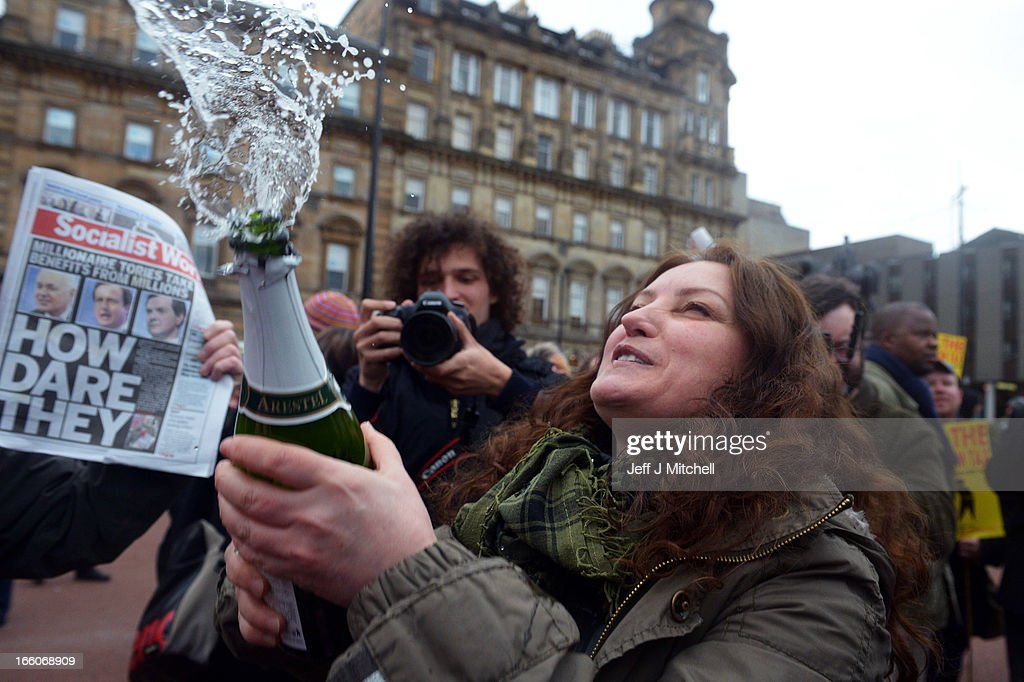 A woman sprays cava as members of the public gather in George Square to mark the death of Baroness Margaret Thatcher on April 8, 2013 in Glasgow, Scotland. It has been confirmed that Lady Thatcher has died this morning following a stroke aged 87. Margaret Thatcher was the first female British Prime Minster and governed the UK from 1979 to 1990. She led the UK through some turbulent years and contentious issues including the Falklands War, the miners' strike and the Poll Tax riots.