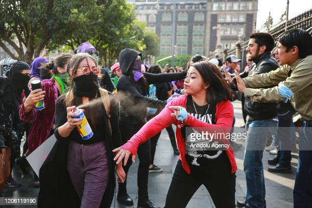 A woman sprays paint to another woman during a protest on the International Women's Day in Mexico City Mexico on March 8 2020