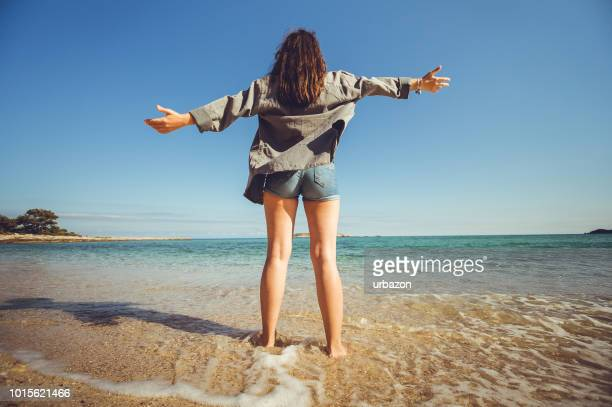 woman spreading arms at the beach - thasos stock photos and pictures