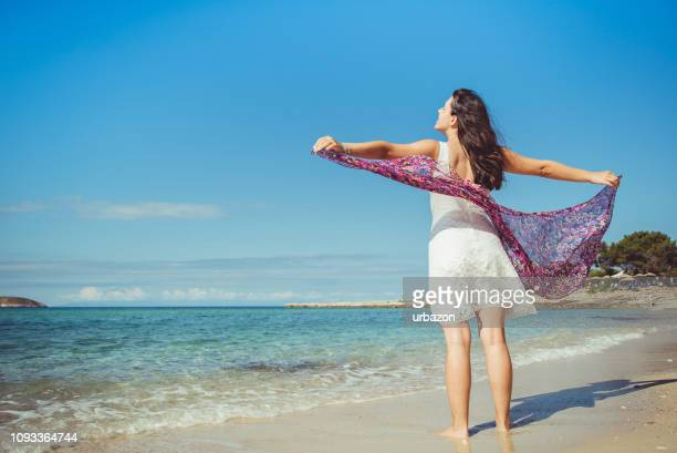 woman spreading arms at the beach - water's edge stock pictures, royalty-free photos & images