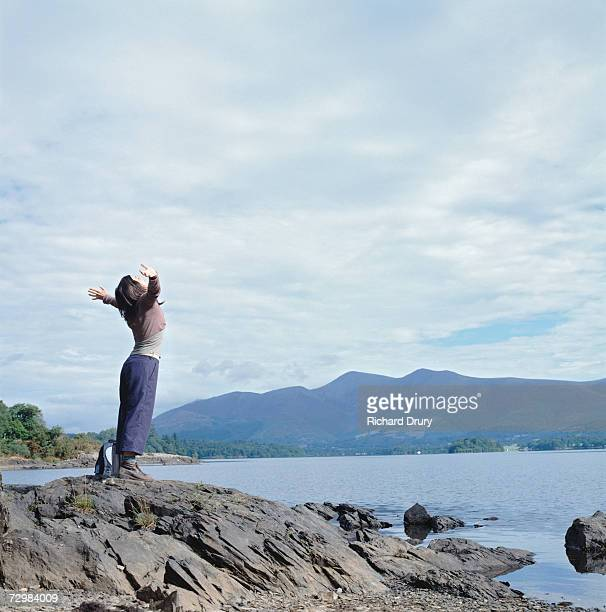 woman spreading arms to sky on lake shore, side view - richard drury stock pictures, royalty-free photos & images