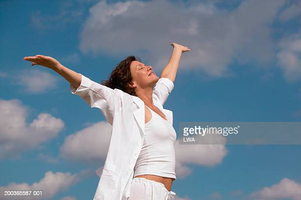 woman spreading arms wide under blue sky, side view - fully unbuttoned stock pictures, royalty-free photos & images