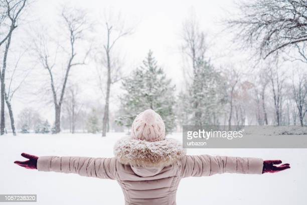 woman spreading hands in a snow covered park - february stock pictures, royalty-free photos & images