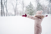young woman spreading hands snow covered