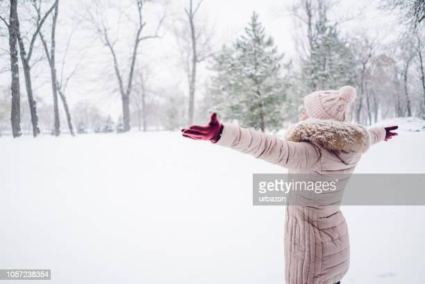 woman spreading hands in a snow covered park - fevereiro imagens e fotografias de stock