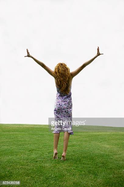Woman Spreading Her Arms in Meadow