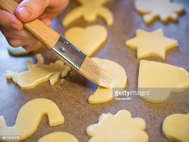 Woman spreading icing on raw Christmas cookies, close-up