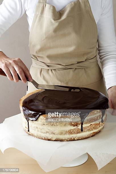 woman spreading melted chocolate on cake - chocolate making stock pictures, royalty-free photos & images