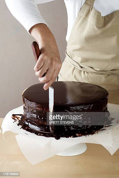 Woman spreading melted chocolate on cake