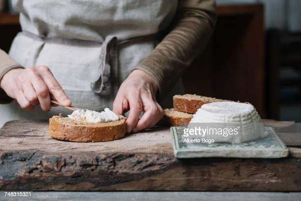 woman spreading ricotta cheese onto slice of bread, mid section - spreading stock pictures, royalty-free photos & images