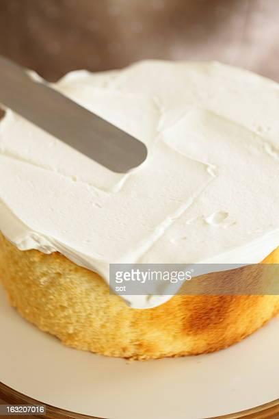 Woman spreading whipped cream on sponge cake