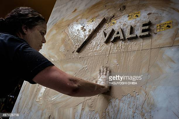 A woman spreads muddy water on the façade of Brazilian mining company Vale headquarters during a protest in Rio de Janeiro Brazil on November 16 2015...