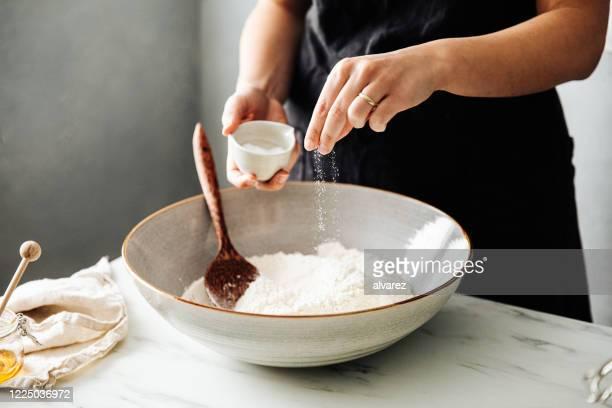 混合する前に小麦粉に塩を振りかける女性 - ペストリー生地 ストックフォトと画像
