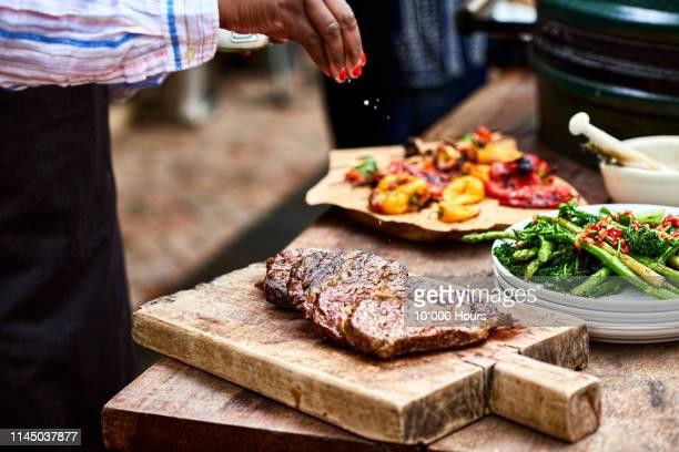 woman sprinkling salt on freshly cooked steak - sal de cozinha - fotografias e filmes do acervo