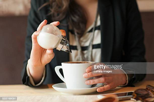 Woman sprinkling sugar in coffee in cafe