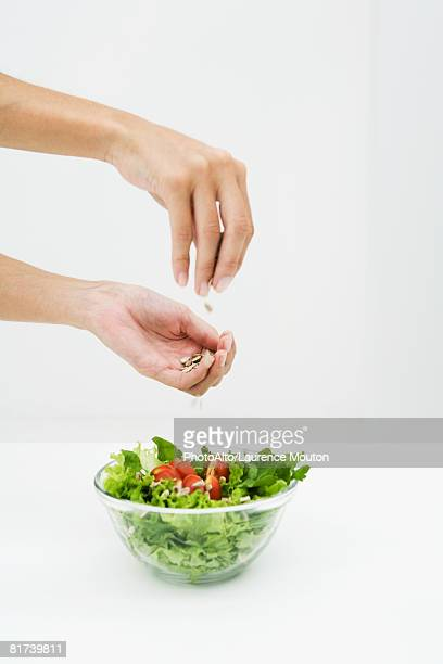 Woman sprinkling sunflower seeds on salad, cropped view of hands