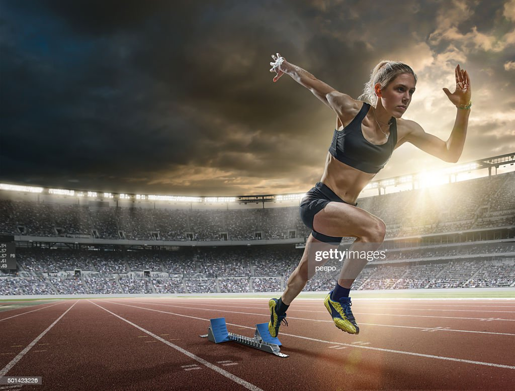 Woman Sprinter in Mid Action Bursting From Blocks During Race : Stock Photo