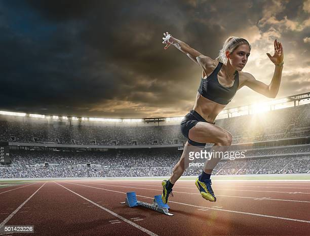 woman sprinter in mid action bursting from blocks during race - athlete stock pictures, royalty-free photos & images
