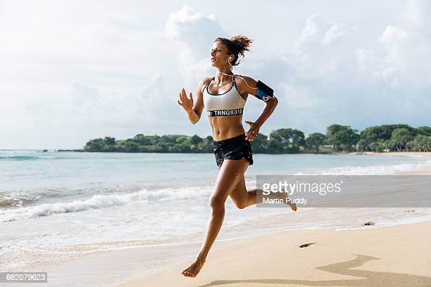woman sprinting along beach with smart phone - sporting term stockfoto's en -beelden