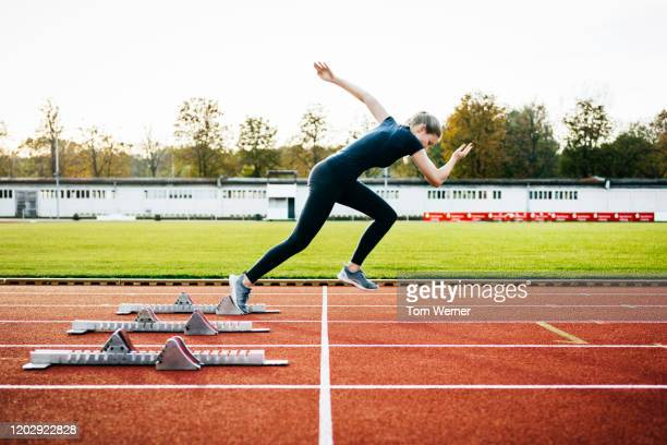 woman sprinting off start line on outdoor running track - sprinting stock pictures, royalty-free photos & images