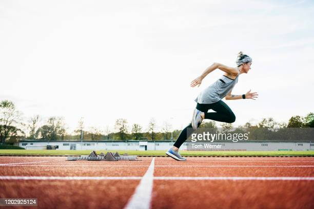 woman sprinting off starting blocks on outdoor running track - sport stock pictures, royalty-free photos & images
