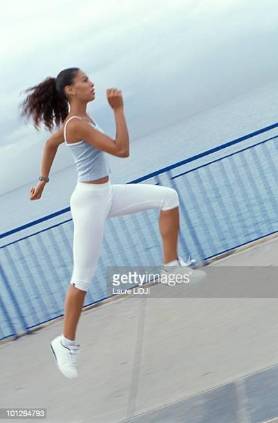 Woman sprinting on sidewalk