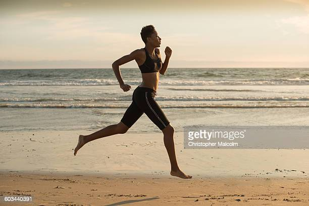 woman sprints on beach at sunset - barefoot stock pictures, royalty-free photos & images