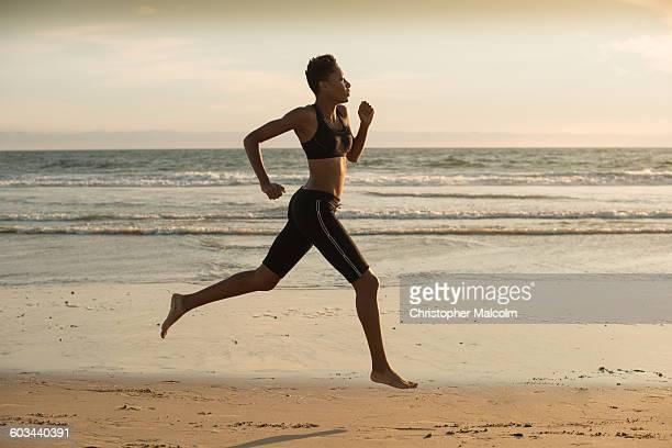 Woman sprints on beach at sunset