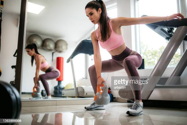 woman squating with kettlebell - manufactured object stock pictures, royalty-free photos & images