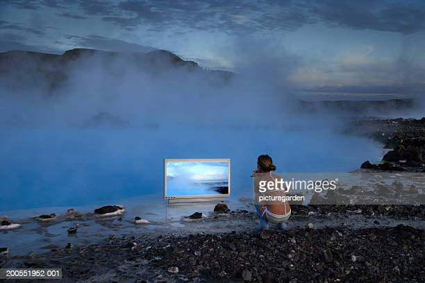 Woman squatting in front of widescreen HD monitor near steaming lagoon, watching, rear view