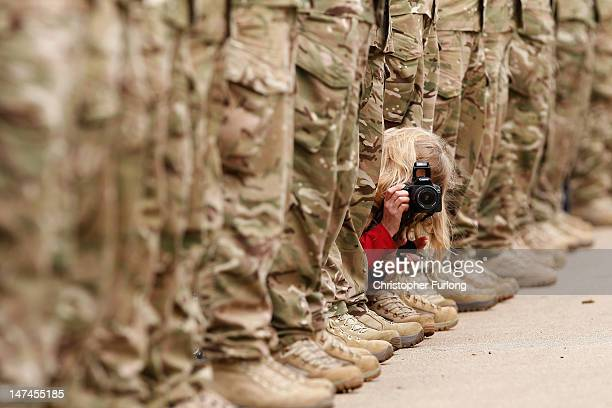 A woman squeezes between an honour guard of soldiers to get a photograph of Johnson Beharry VC carrying the Olympic torch at the National War...