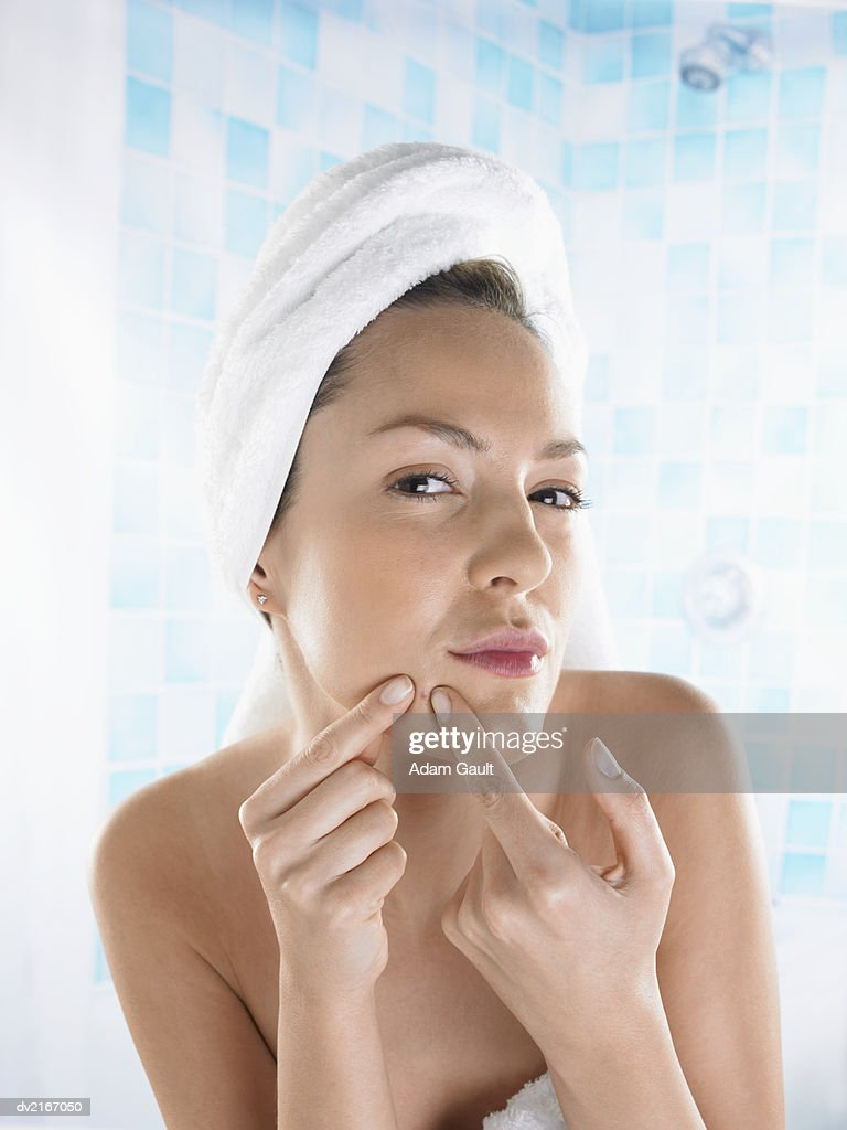 Woman Squeezing a Pimple on Her Chin : Stock Photo